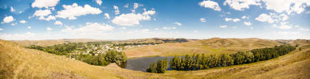 hilly: Summer panorama of the hilly terrain of the steppe lake, trees and village.