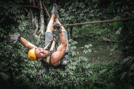 Man zipline flight in jungle Stock Photo