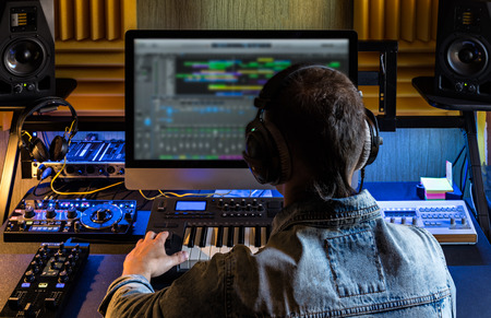 Men produce electronic music in project home studio. 版權商用圖片