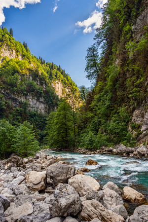 The mountain river flows among the rocks in the mountain gorge Stock Photo