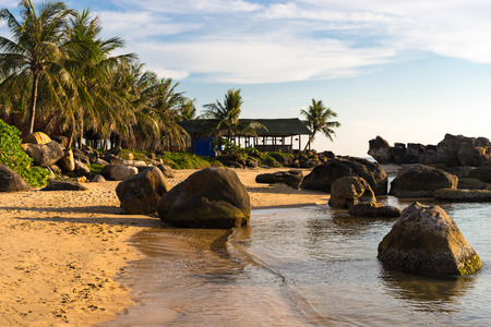 Seashore with stones in water on coastline at sunset on Long Beach of Phu Quoc island in Vietnam