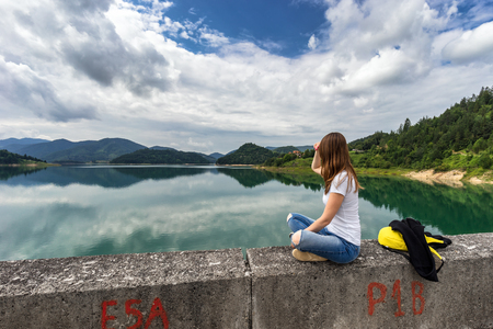 Young woman sitting and looking on Zaovine lake in Serbia