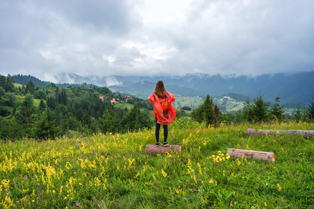 Woman tourist in raincoat travels outdoors and standing on view point on height and looking on hills and clouds in summer overcast day in Serbia