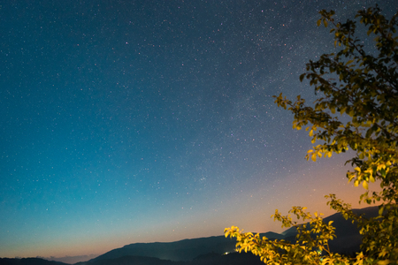 Colored night sky with stars in mountains