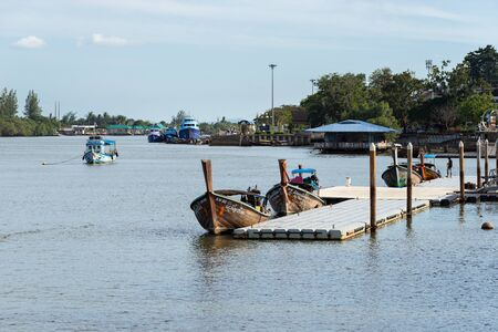 KRABI TOWN, THAILAND - JANUARY 11, 2019: Pier and authentic local long tail Thai boats in the water moored to a floating pontoon 新聞圖片