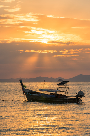 Golden sun rays and local empty thai long-tail boat under them in sea water at beautiful orange sunset