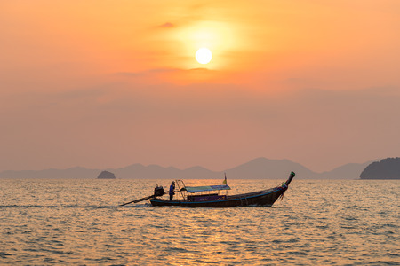 Ao Nang, Krabi Province, Thailand - January 14, 2019: Local fisherman float on thai longtail boat in the sea water at beautiful orange sunset Редакционное