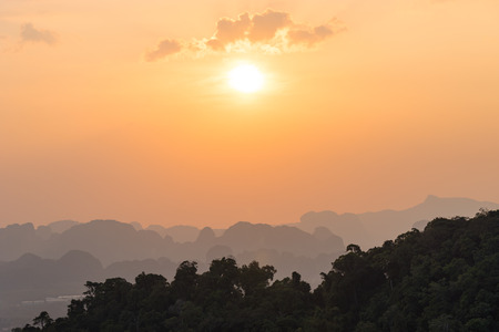 Beautiful orange sunset in Asian jungle with misty outlines of mountains in the distance