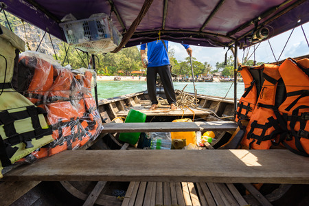 Inside in thai longtail boat. View of empty seats for passengers and life jackets. The sailor controls the boat and sails from the shore to the sea
