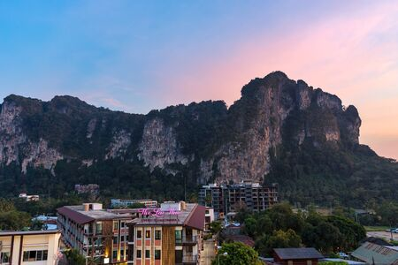 Ao Nang, Krabi Province, Thailand - January 22, 2019: View on big cliff and hotels buildings in the evening at sunset twilight