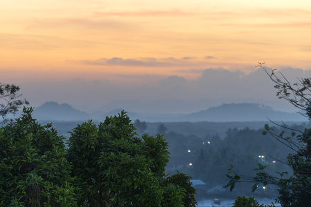 Sunrise orange sky and foggy hills and trees on horizon in the early morning in Krabi Town in Thailand