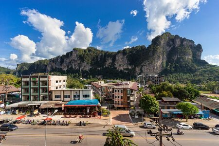 Ao Nang, Krabi Province, Thailand - January 13, 2019: View from the height on local main road and street with hotels, restaurants, big cliff and clouds on blue sky in sunny day