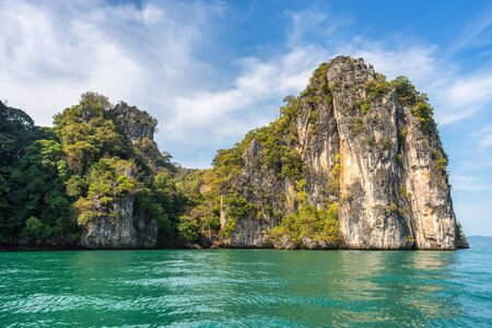 Picturesque rock covered with tropical greenery in the water of the azure Andaman sea on Hong island in Thailand under the blue sky
