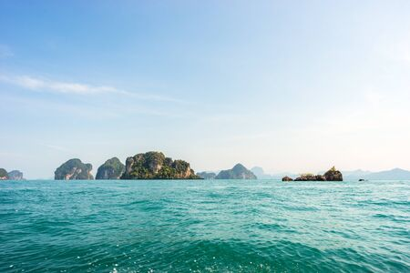 Seascape of tropical islands with cliffs and mountains covered by greenery in azure sea  water under blue sky in sunny day in Thailand