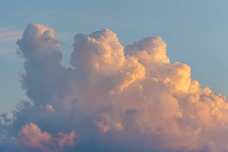 Beautiful colored dramatic cumulus fluffy clouds on blue sky at sunset