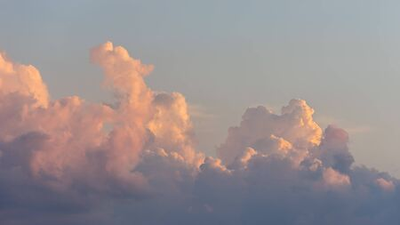 Close up view of beautiful colored cumulus fluffy clouds with pink and purple hues in the blue sky at sunset background