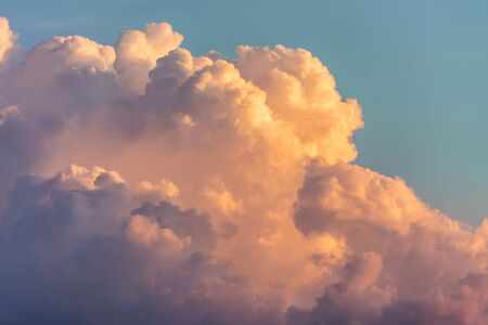 Close up view of beautiful colored dramatic cumulus fluffy clouds on blue sky at sunset background