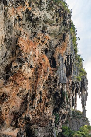 Big textured natural limestone cliffs with stone icicles formations on Phra Nang beach on Railay in Krabi in Thailand Banco de Imagens
