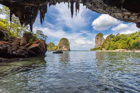 Phra Nang beach, Peninsula Railay, Krabi Province, Thailand - January 18, 2019: Seascape view from Phra Nang cave on blue sky with beautiful clouds, beach and tropical island in water at day time