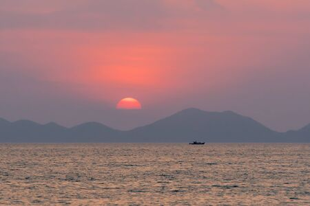 Picturesque seascape at sunset. Large red circle of sun in a haze sets behind the silhouette of the mountains and clouds on the sea horizon Banco de Imagens