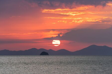 Picturesque sunset on sea. Large red circle of sun sets behind the silhouette of the mountains and clouds above the sea horizon