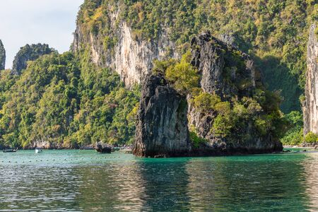 Cliff covered by tropical greenery and trees in turquoise sea water near beach on Koh Hong island in Krabi in Thailand