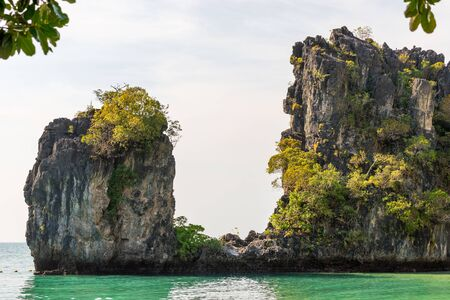 Cliff covered by tropical greenery and trees in sea water near beach on Koh Hong island in Krabi in Thailand