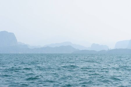 Blue sea water and shapes of mountain range silhouettes on horizon in haze