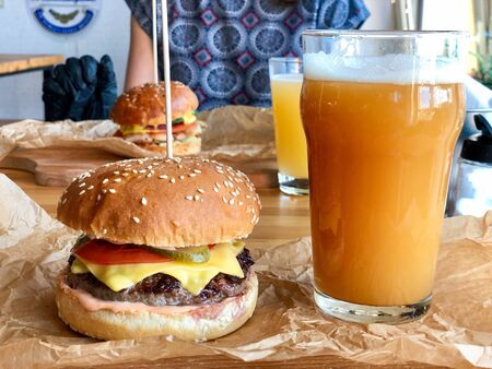 Fresh craft beer in glass and juicy burger