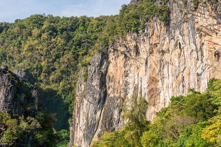 Big orange limestone cliff covered by tropical greenery Banco de Imagens