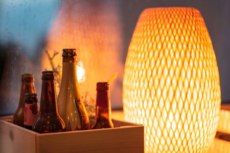 Elements of cozy decor in beer craft pub in the evening: warm light from lamp and empty bottles in wooden box. Close-up view. Banco de Imagens