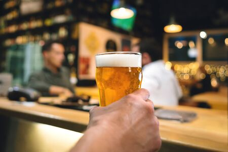 A glass of light beer in hand is served to the visitor of the craft pub. Focus on foreground with bokeh on blurred background