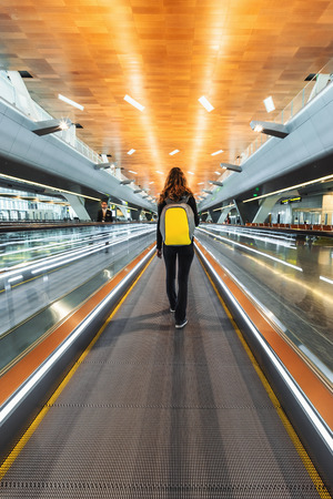 DOHA, QATAR - JANUARY 23, 2019: One woman traveller with backpack go on moving walkway travolator in new Hamad International Airport. Back view