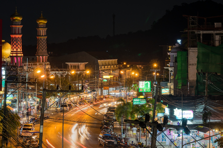 Ao Nang, Krabi Province, Thailand - January 21, 2019: Muslim temple, hotels, restaurants and markets on local main street and lights of transport on road in the night. Long exposure shot