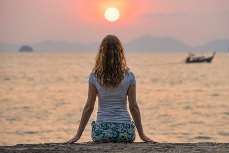 Young woman sits alone on seashore and looks on beautiful scarlet sunset and seascape in Krabi. Back view.