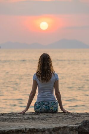 One young woman sits on seashore and looks on beautiful scarlet sunset and seascape in Krabi. Back view.