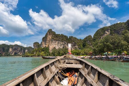 Front bow of the wood thai longtail boat, floating on the sea to the beautiful Railay Beach in Thailand in sunny day under blue sky
