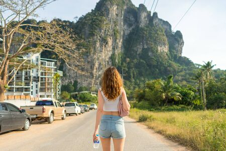 One beautiful young woman goes forward on the road in tropical country. Rear view