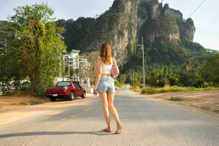 One young tourist woman stands on the road and looks on big tropical mountain in Krabi Province in Thailand. Rear view