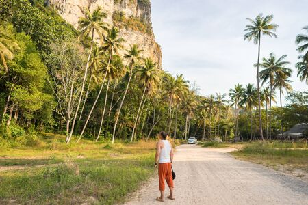 One young tourist man stands on the road between the palm trees and looks on big tropical mountain in Krabi Province in Thailand. Back view 版權商用圖片