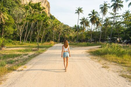 One beautiful young slender woman goes forward on the road in tropical country. Rear view