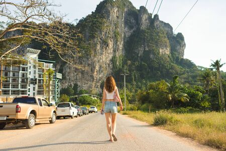 One young traveller woman goes forward on the road to mountain in Krabi Province in Thailand. Back view Banco de Imagens
