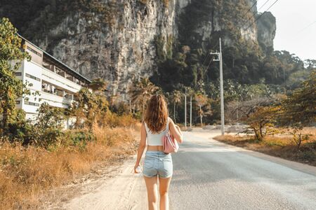 One beautiful young woman goes ahead on the road in tropical country. Back view