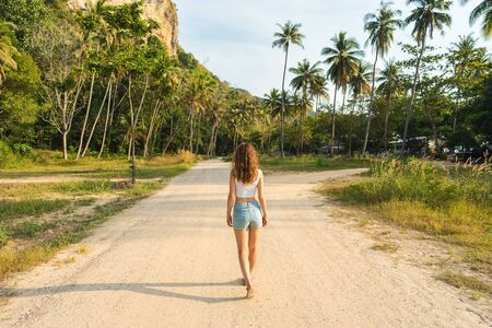 One beautiful young woman goes forward on the road between pal trees in tropical country. Rear view Banco de Imagens