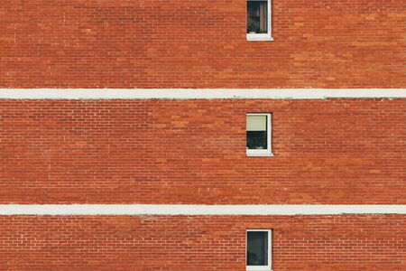 Red brick wall of the house building with windows. Background with space for text