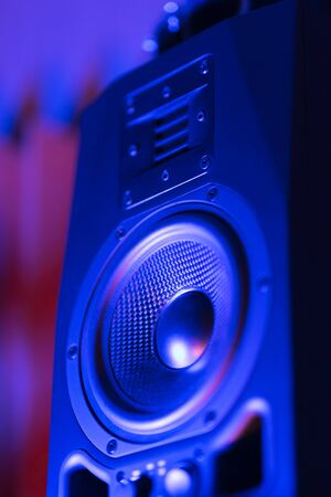 Music loudspeaker sound system in neon blue light. Dynamic monitor in studio close-up