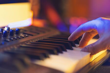 Produce electronic music in studio and playing on midi keyboard by hand Standard-Bild - 138446156