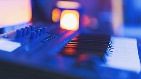 Midi keyboard in home studio in blue neon light. Shallow depth of field