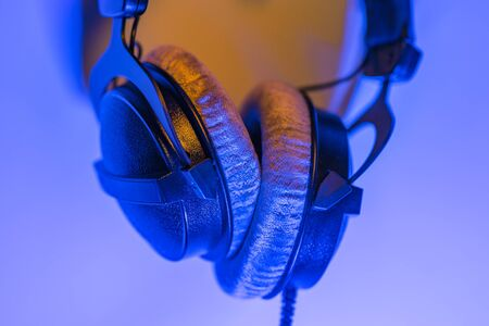 Professional headphones on blue purple background with space for copy