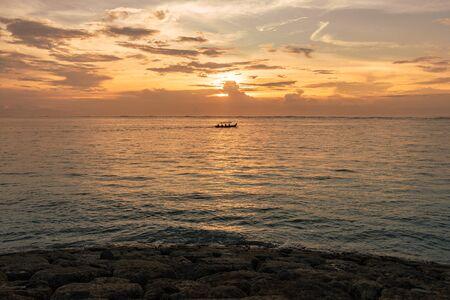 Beautiful orange sunset seascape with boat on horizon on Bali in Indonesia